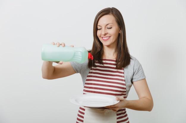 Młoda gospodyni w pasiastym fartuchu odizolowywającym. gospodyni trzyma butelkę z płynem czyszczącym do mycia naczyń, biały pusty okrągły talerz