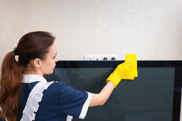 Młoda gospodyni w schludnym mundurze i żółtych rękawiczkach odkurza telewizor szmatką, z bliska widok z tyłu