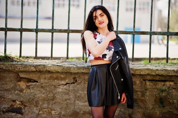 Młoda gotycka dziewczyna na czarnej skórzanej spódnicy, kurtce i punkowych szpilkach na żelaznym ogrodzeniu.