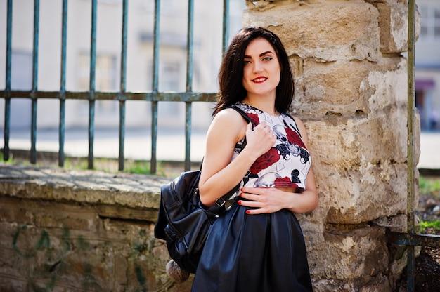 Młoda gotycka dziewczyna w czarnej skórzanej spódnicy i punkowych szpilkach na wysokim obcasie z plecakiem postawionym na żelaznym ogrodzeniu.
