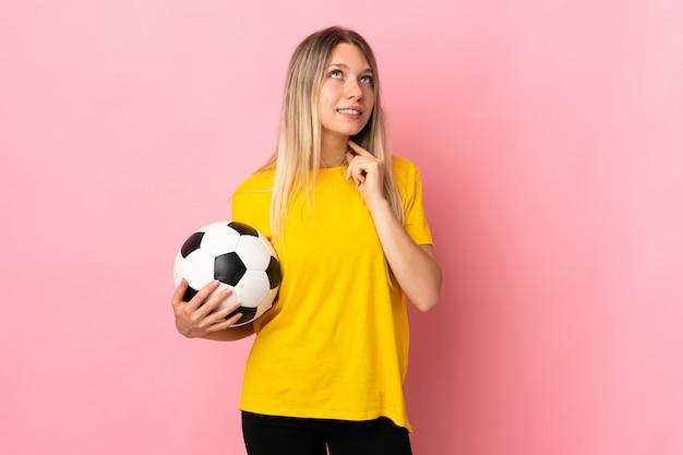 Młoda gracz futbolu kobieta odizolowywająca na menchii ścianie myśleć pomysł