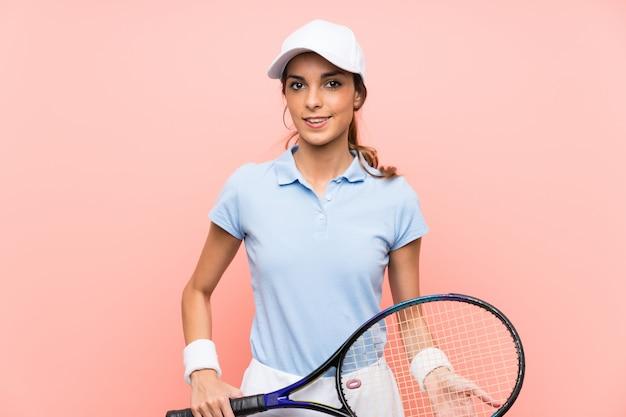 Młoda gracz w tenisa kobieta nad menchii ścianą