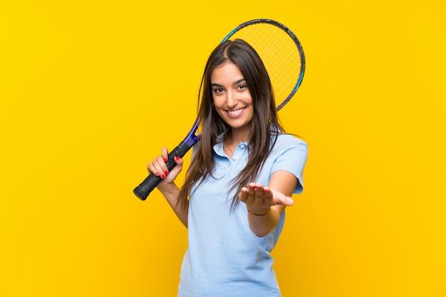 Młoda gracz w tenisa kobieta nad odosobnioną kolor żółty ścianą zaprasza przychodzić z ręką. cieszę się, że przyszedłeś