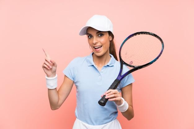 Młoda gracz w tenisa kobieta nad odosobnioną menchii ścianą zaskakującą i wskazuje palec z boku
