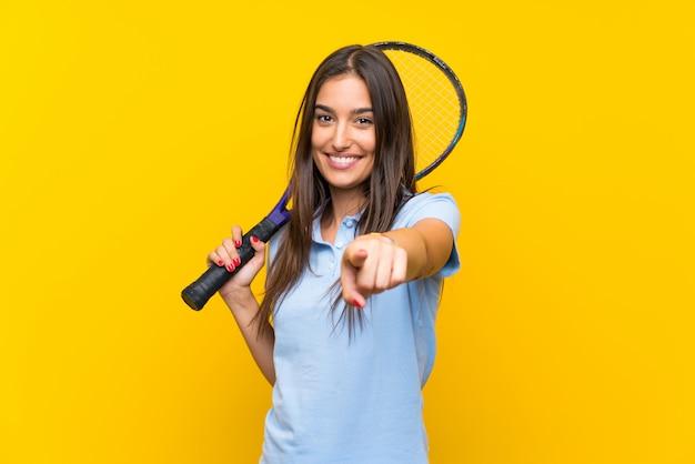 Młoda gracz w tenisa kobieta nad odosobnionymi żółtymi ściana punktami dotyka ciebie z ufnym wyrażeniem