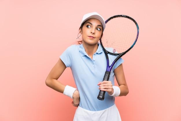 Młoda gracz w tenisa kobieta robi wątpliwości gestowi podczas gdy podnoszący ramiona
