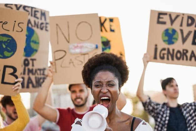 Młoda grupa demonstrantów na drogach z różnych kultur i ras walczących o zmiany klimatyczne - skup się na twarzy afrykańskiej kobiety