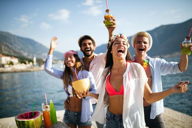 Młoda grupa przyjaciół cieszących się latem na plaży o zachodzie słońca