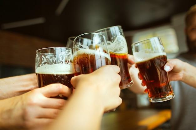 Młoda grupa przyjaciół pijąca piwo, bawiąca się śmiejąc się i świętując razem z bliska, brzęcząc