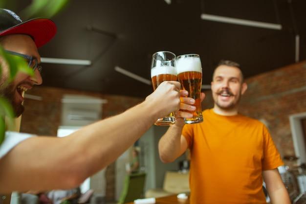 Młoda grupa przyjaciół pijąca piwo, bawiąca się, śmiejąca się i świętująca razem. dwóch mężczyzn stuka się szklankami piwa. oktoberfest, przyjaźń, wspólnota, koncepcja szczęścia.
