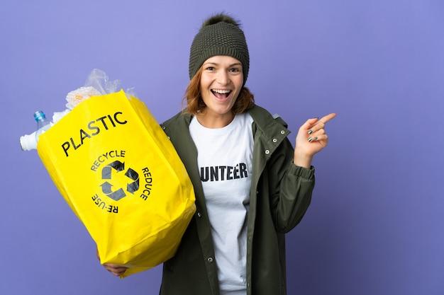 Młoda gruzinka trzymająca torbę pełną plastikowych butelek do recyklingu, zamierzająca znaleźć rozwiązanie, podnosząc palec do góry