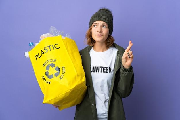 Młoda gruzinka trzymająca torbę pełną plastikowych butelek do recyklingu ze skrzyżowanymi palcami i życząca wszystkiego najlepszego