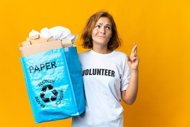Młoda gruzinka trzymająca worek pełen papieru do recyklingu, trzymając kciuki i życząc wszystkiego najlepszego
