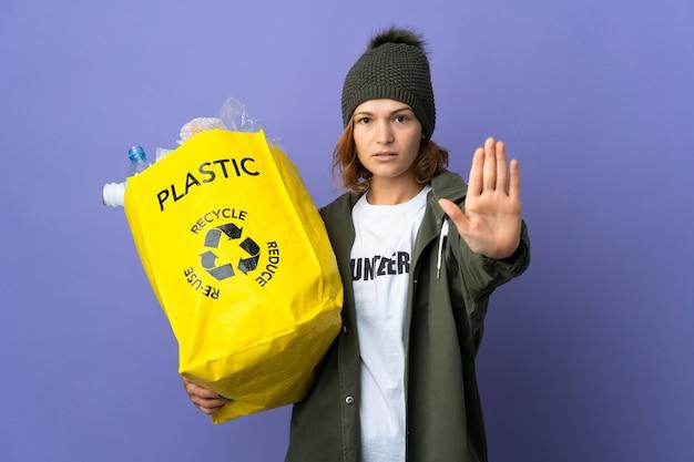 Młoda gruzińska dziewczyna trzyma torbę pełną plastikowych butelek do recyklingu, czyniąc gest stopu