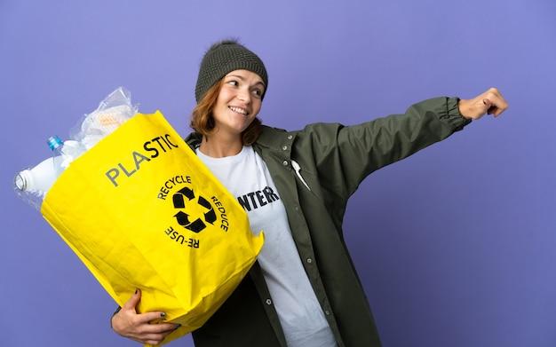 Młoda gruzińska dziewczyna trzyma torbę pełną plastikowych butelek do recyklingu, dając gest kciuki do góry