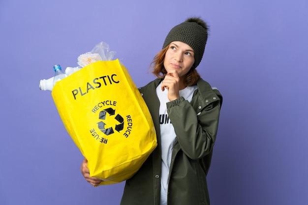 Młoda gruzińska dziewczyna trzyma torbę pełną plastikowych butelek do recyklingu i patrząc w górę