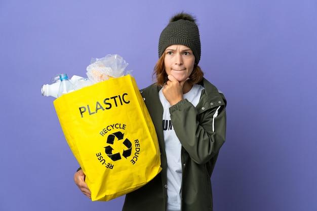 Młoda gruzińska dziewczyna trzyma torbę pełną plastikowych butelek do recyklingu, mając wątpliwości i myśli