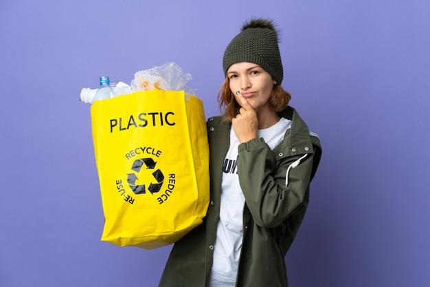 Młoda gruzińska dziewczyna trzyma torbę pełną plastikowych butelek do recyklingu, mając wątpliwości, patrząc w górę
