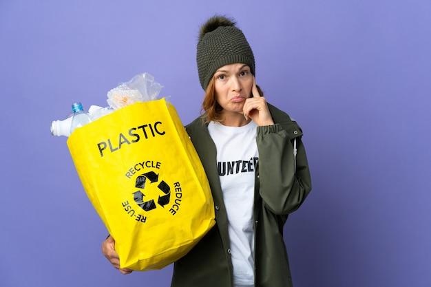 Młoda gruzińska dziewczyna trzyma torbę pełną plastikowych butelek do recyklingu myśli pomysł