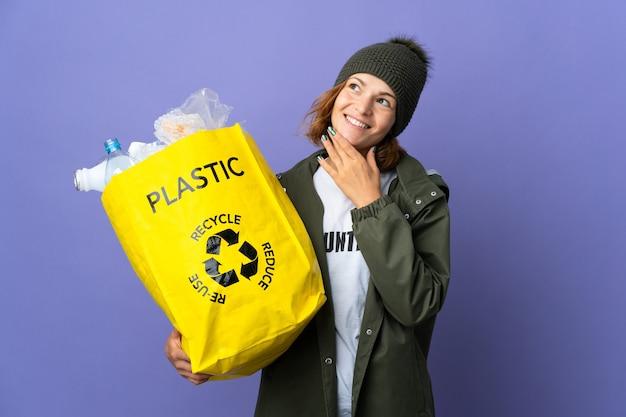 Młoda gruzińska dziewczyna trzyma torbę pełną plastikowych butelek do recyklingu, patrząc w górę, uśmiechając się