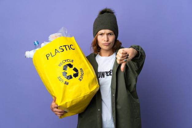 Młoda gruzińska dziewczyna trzyma torbę pełną plastikowych butelek do recyklingu, pokazując kciuk w dół z negatywnym wyrazem twarzy