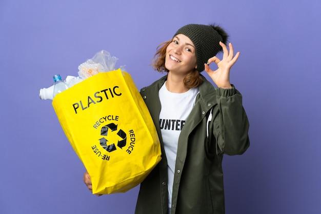 Młoda gruzińska dziewczyna trzyma torbę pełną plastikowych butelek do recyklingu, pokazując palcami znak ok