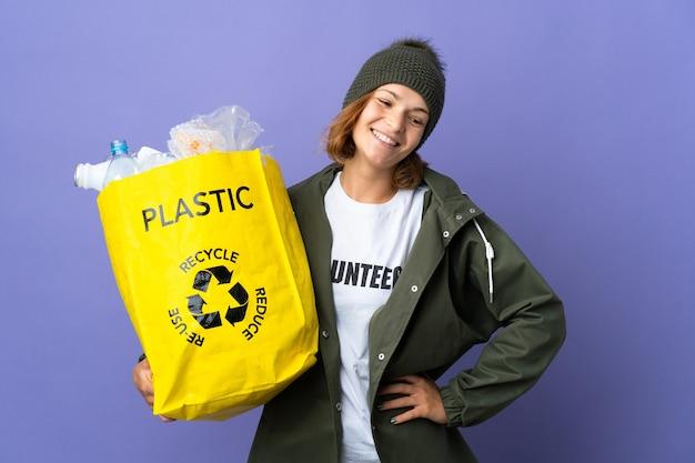 Młoda gruzińska dziewczyna trzyma torbę pełną plastikowych butelek do recyklingu, pozowanie z rękami na biodrze i uśmiechnięta