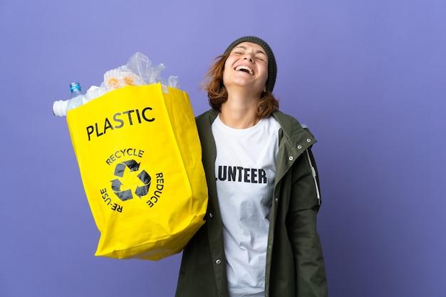 Młoda gruzińska dziewczyna trzyma torbę pełną plastikowych butelek do recyklingu, śmiejąc się