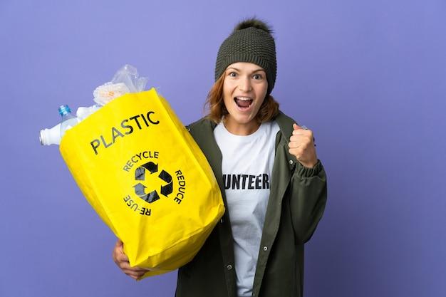Młoda gruzińska dziewczyna trzyma torbę pełną plastikowych butelek do recyklingu, świętując zwycięstwo na pozycji zwycięzcy
