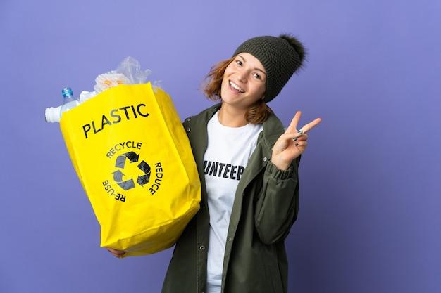 Młoda gruzińska dziewczyna trzyma torbę pełną plastikowych butelek do recyklingu, uśmiechając się i pokazując znak zwycięstwa