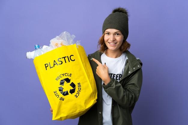 Młoda gruzińska dziewczyna trzyma torbę pełną plastikowych butelek do recyklingu, wskazując na bok, aby zaprezentować produkt