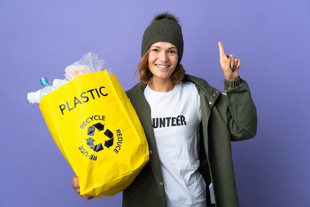 Młoda gruzińska dziewczyna trzyma torbę pełną plastikowych butelek do recyklingu, wskazując na świetny pomysł