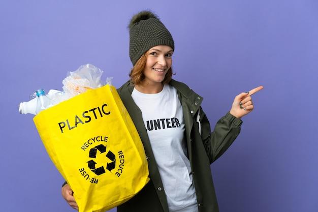 Młoda gruzińska dziewczyna trzyma torbę pełną plastikowych butelek do recyklingu, wskazując wstecz