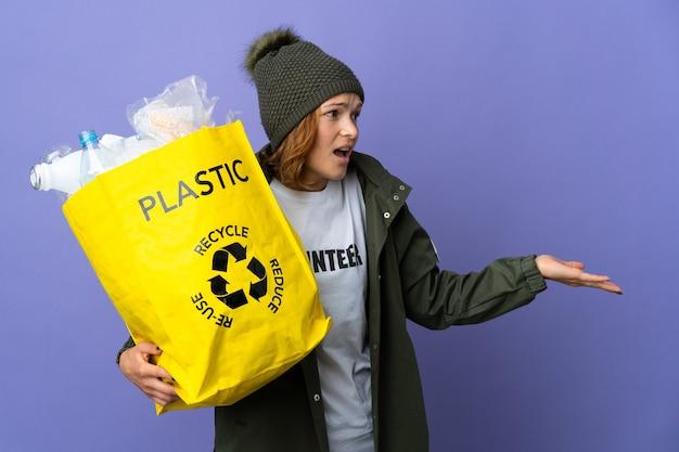 Młoda gruzińska dziewczyna trzyma torbę pełną plastikowych butelek do recyklingu z wyrazem zaskoczenia, patrząc z boku