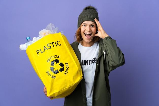 Młoda gruzińska dziewczyna trzyma torbę pełną plastikowych butelek do recyklingu z zaskoczeniem