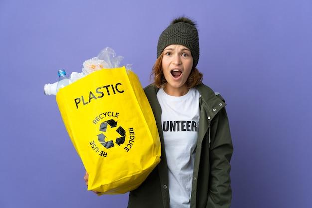 Młoda gruzińska dziewczyna trzyma torbę pełną plastikowych butelek do recyklingu z zaskoczonym wyrazem twarzy