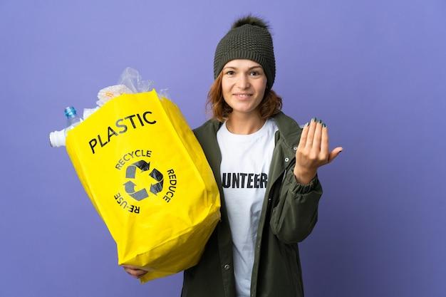 Młoda gruzińska dziewczyna trzyma torbę pełną plastikowych butelek do recyklingu zaprasza do przyjścia z ręką. cieszę się, że przyszedłeś