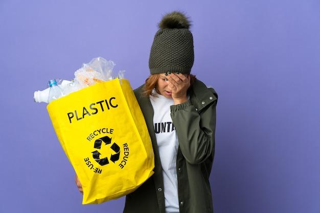 Młoda gruzińska dziewczyna trzyma torbę pełną plastikowych butelek do recyklingu ze zmęczonym i chorym wyrazem twarzy