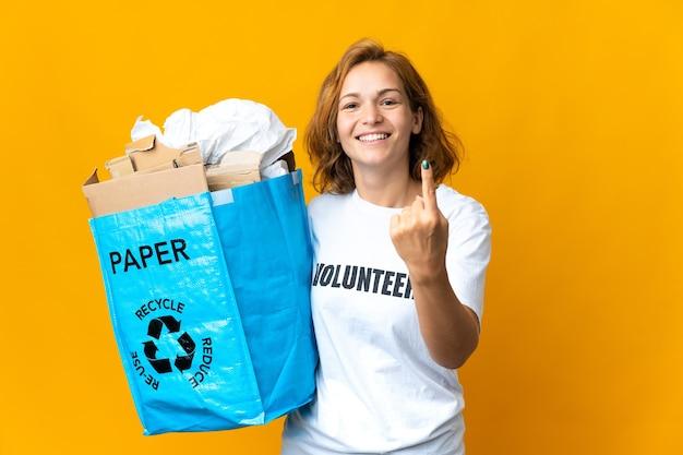 Młoda gruzińska dziewczyna trzyma worek recyklingu pełnego papieru do recyklingu, robi nadchodzący gest