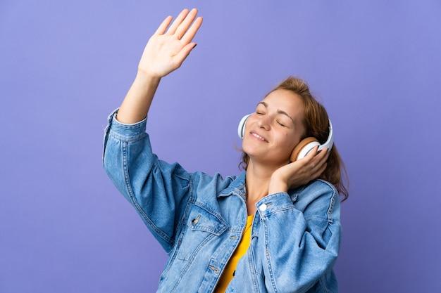 Młoda gruzińska kobieta na białym tle na fioletowym tle słuchania muzyki i tańca