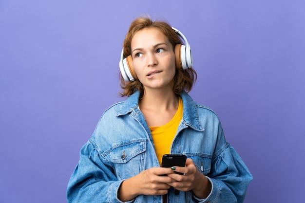 Młoda gruzińska kobieta na fioletowej ścianie słuchanie muzyki z telefonu komórkowego i myślenia