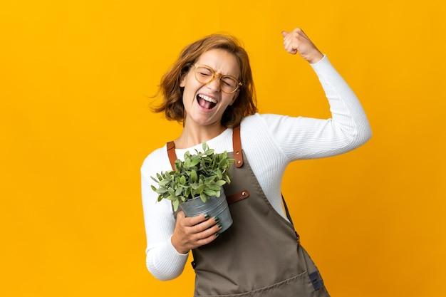 Młoda gruzińska kobieta trzyma roślinę na białym tle na żółtej ścianie świętuje zwycięstwo