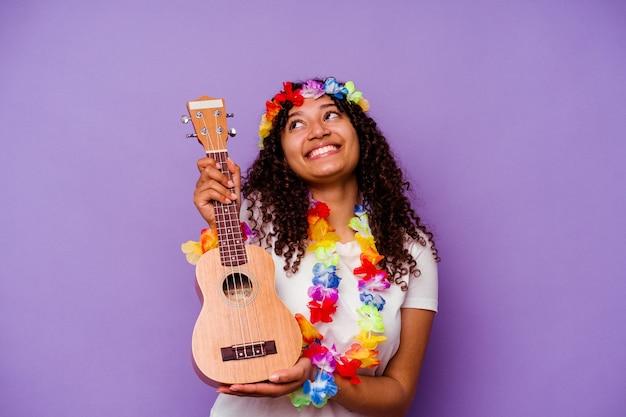 Młoda hawajska kobieta gra na ukelele na białym tle na fioletowym tle