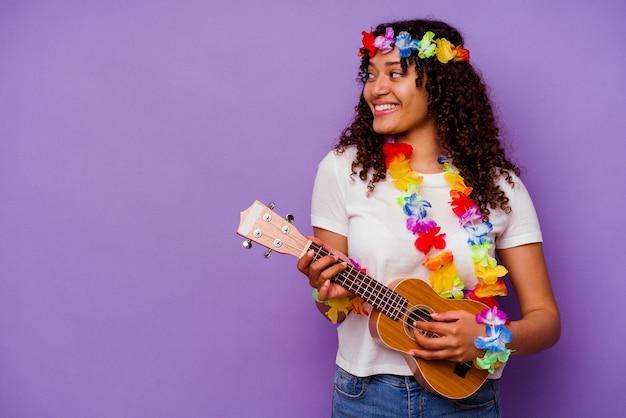 Młoda hawajska kobieta grająca na ukelele na fioletowym tle