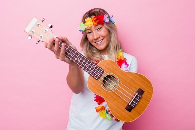 Młoda hawajska kobieta grająca na ukulele na białym tle