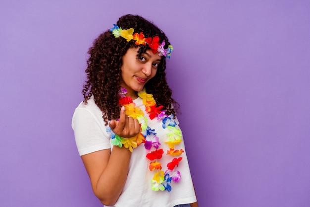 Młoda hawajska kobieta na białym tle na fioletowym tle, wskazując palcem na ciebie, jakby zapraszając podejdź bliżej.