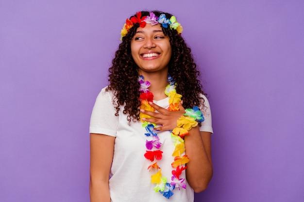 Młoda hawajska kobieta na fioletowej ścianie śmieje się głośno, trzymając rękę na piersi.
