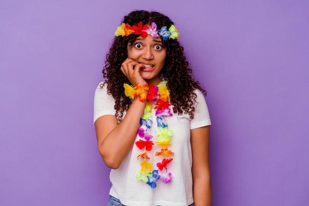 Młoda hawajska kobieta na fioletowym tle gryzie paznokcie, nerwowa i bardzo niespokojna.