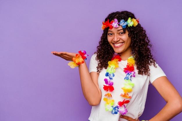 Młoda hawajska kobieta na fioletowym tle pokazująca miejsce na dłoni i trzymająca drugą rękę na pasie.