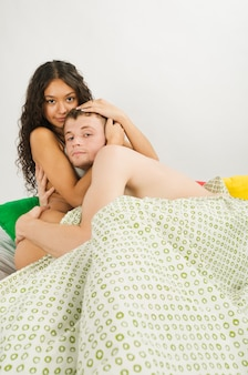 Młoda heteroseksualna para rasy kaukaskiej w łóżku w domu